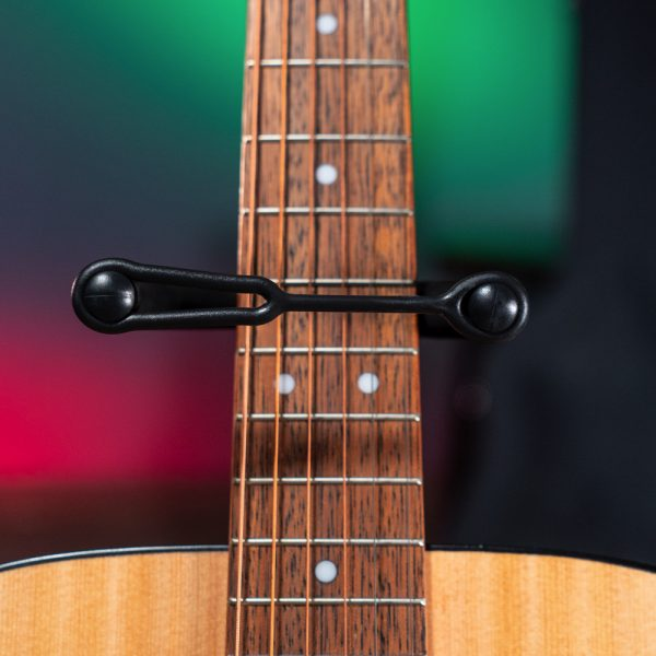 closeup of fretboard of acoustic guitar on Stageline stand